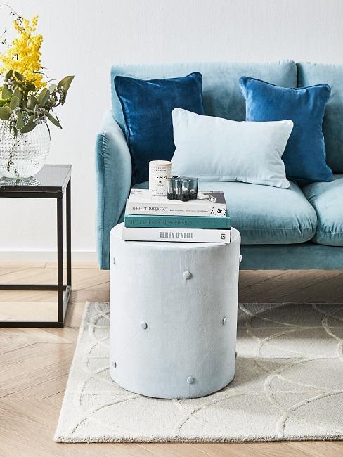 Ein kleines blaues Samtsofa in einem kleinen Wohnzimmer mit einem Pouf als Beistelltisch
