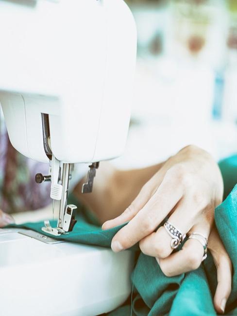 Moderne Nähmaschine, an der eine Frau gerade mit grünem Stoff näht