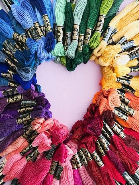 Viele bunte Fäden, farblich geordnet und zu einem Regenbogenherz zusammengelegt