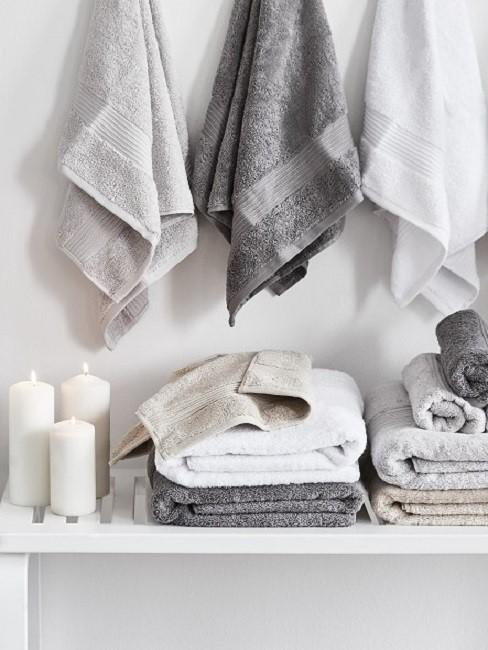 Handtücher in Weiß und Grau neben Kerzen auf einer Ablage und darüber hängend