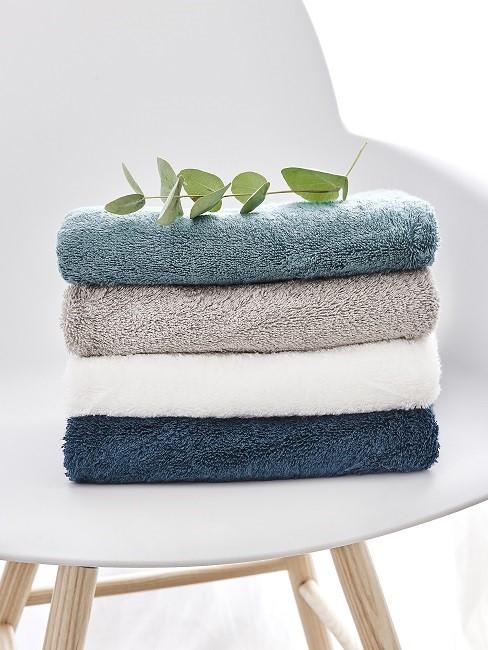 Weißer Stuhl mit einem Stapel Handtücher