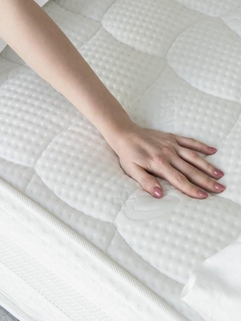 Frauenhand auf weißer Matratze