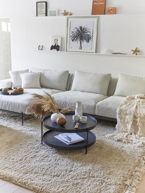 Helles Wohnzimmer mit hellem Sofa und Teppich, über dem Sofa zwei Wandregale mit schöner Deko