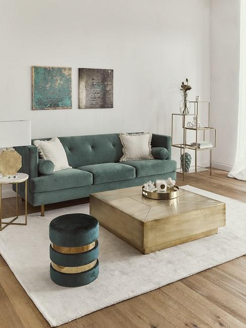 Grünes Sofa vor einem hellen Teppich, darüber zwei Wandbilder nebeneinander