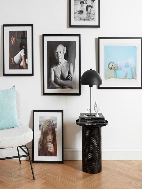 Wohnzimmer mit einem Sessel und einem Beistelltisch, als Wanddeko viele Bilder als Collage