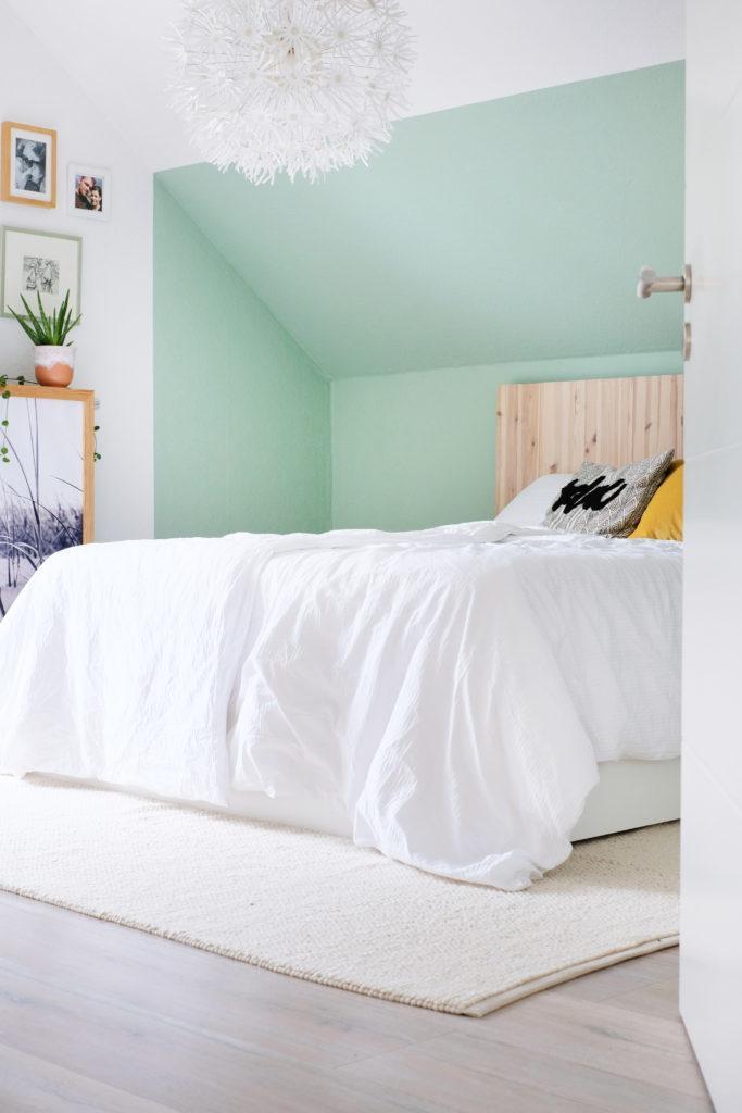 Bett vor grüner Wand