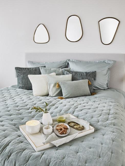 Helles Bett mit Samt-Bettwäsche in einem hellen Aqua-Ton