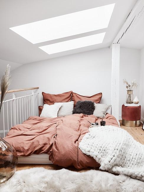 Bett in einem hellen Dachraum mit sommerlich leichter Bettwäsche in Braun