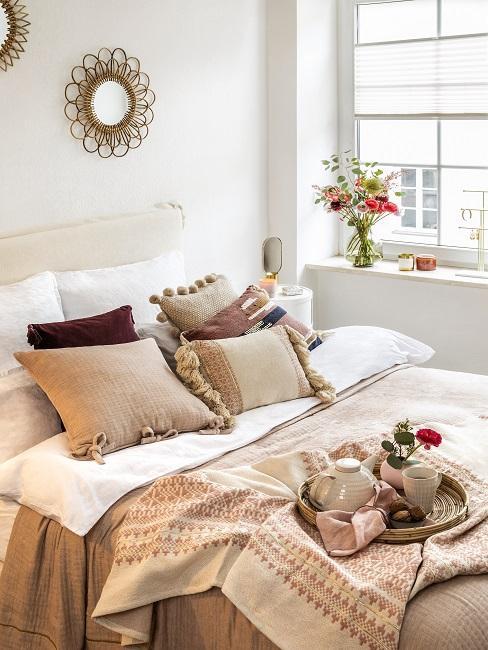 Schlafzimmer mit einem Bett neben dem Fenster, die Bettwäsche ist aus sommerlichem Leinen Material