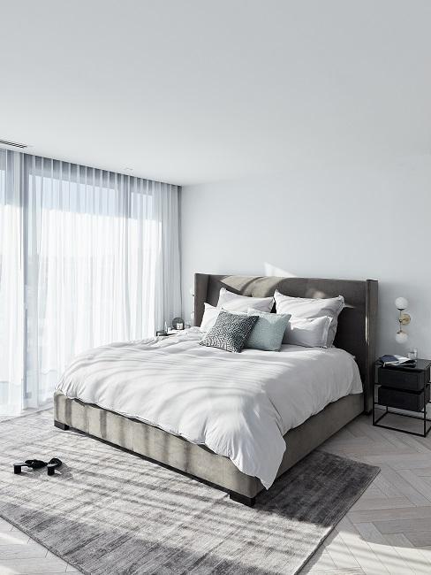 Designer Schlafzimmer mit grauem Boxspringbett, schwarzem Beistelltisch und grauem Teppich