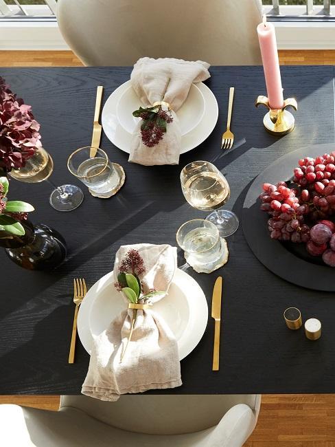 Gedeckter schwarzer Tisch mit Deko
