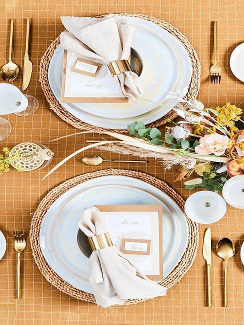 Natürliches Tischgedeck mit goldenen Elementen und Platzkarten