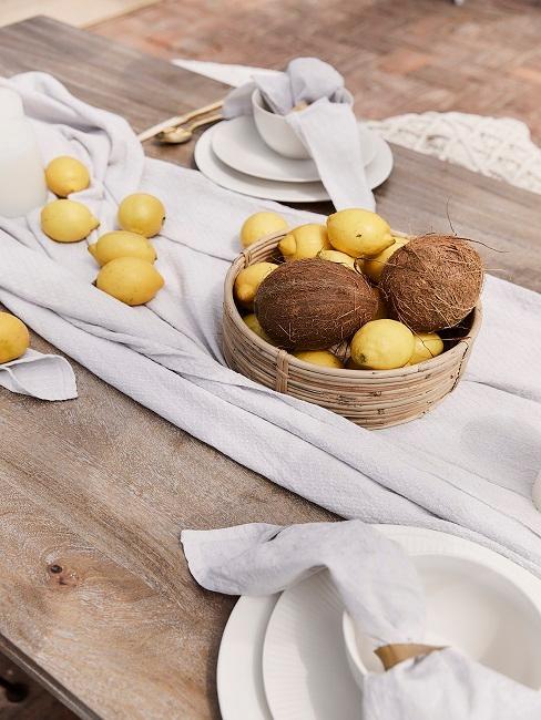 Holztisch mit Zitronen und Kokosnüssen