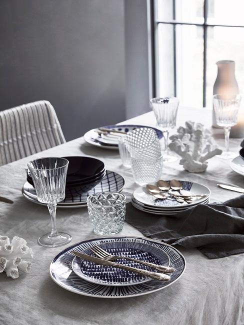 Grau gedeckter Esstisch mit blauen Elementen