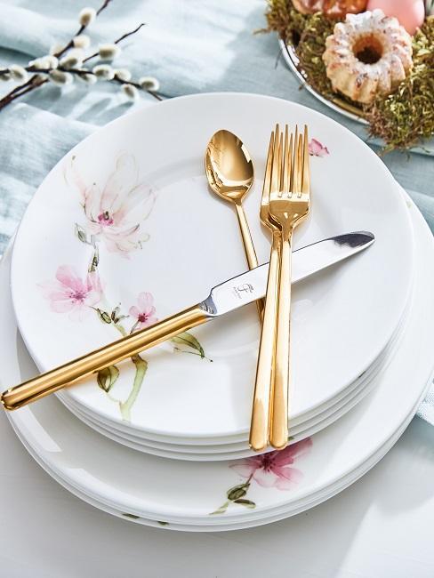Goldenes Besteck auf Tellern mit Blumenverzierung