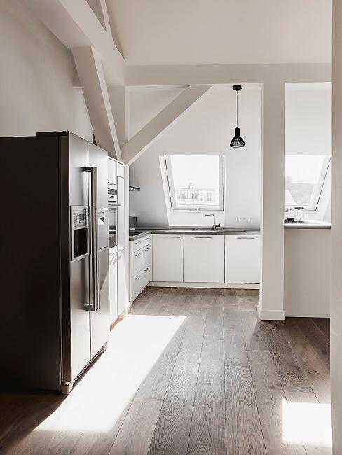 Offene Luxus Küche mit Dachschräge in Weiß mit Elektrogeräten in Schwarz als Kontrast