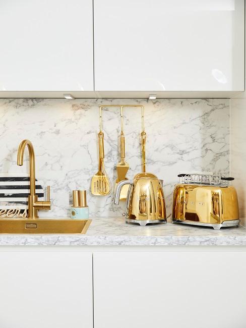 Küchenablage aus Marmor mit Toaster, Wasserkocher und weiteren Küchenutensilien in Gold
