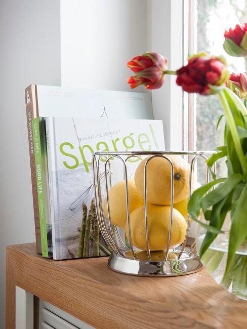 Fensterbrett mit Rezeptbüchern, Obstkorb und Blumen