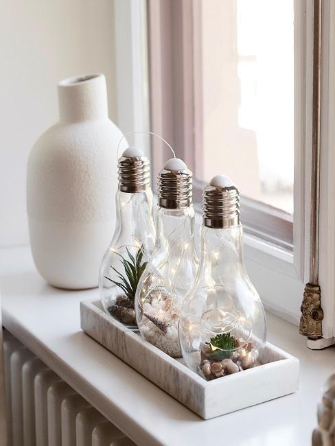 Fensterbrett mit dekorativ befüllten Glühbirnen auf einem Tablett als Dekoration neben einer Vase