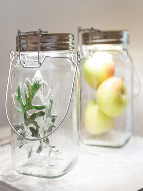 Zwei leuchtende Sonnengläser, eines mit Thymian befüllt, eines mit Äpfeln, ideal zur Fenster Dekoration auf dem Fensterbrett