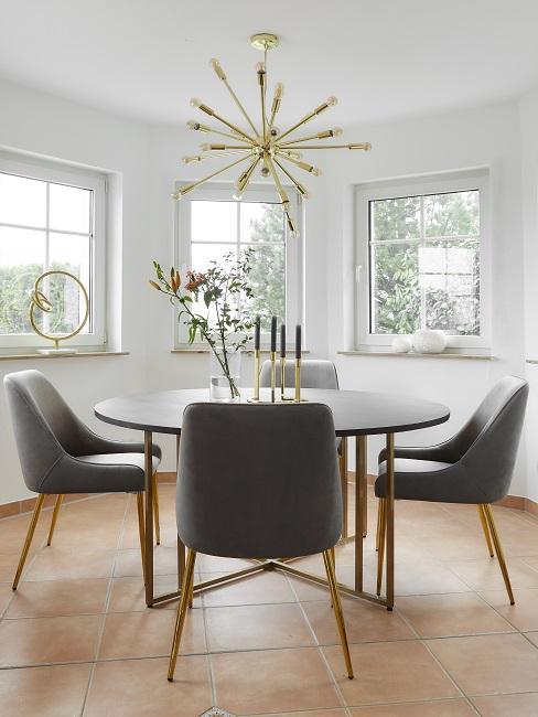 Lagom Wohntrend Esszimmer mit rundem Holztisch, grauen Stühlen und goldener Pendelleuchte