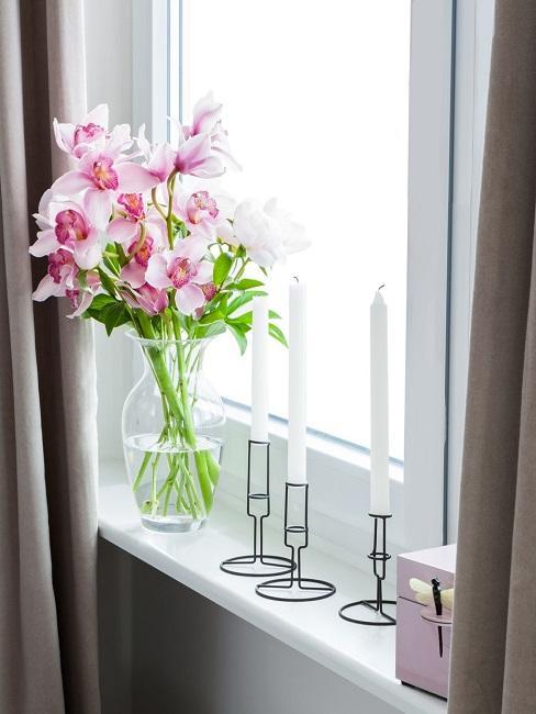 Fensterbrett mit Blumenvase und Kerzen im Kerzenständer