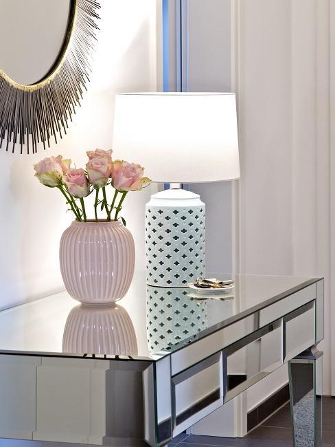 Spiegel Konsole mit einer Blumenvase und einer Tischlampe als Deko im Wohnzimmer