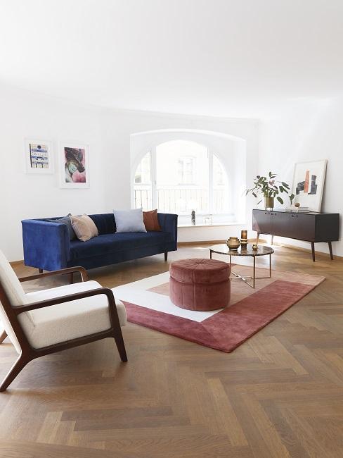 Stilmix Wohnzimmer blaues Sofa, weißer Sessel und roter Teppich