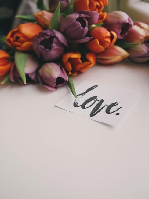 Valentinstag Sprüche Blumen neben Karte mit Schriftzug Love
