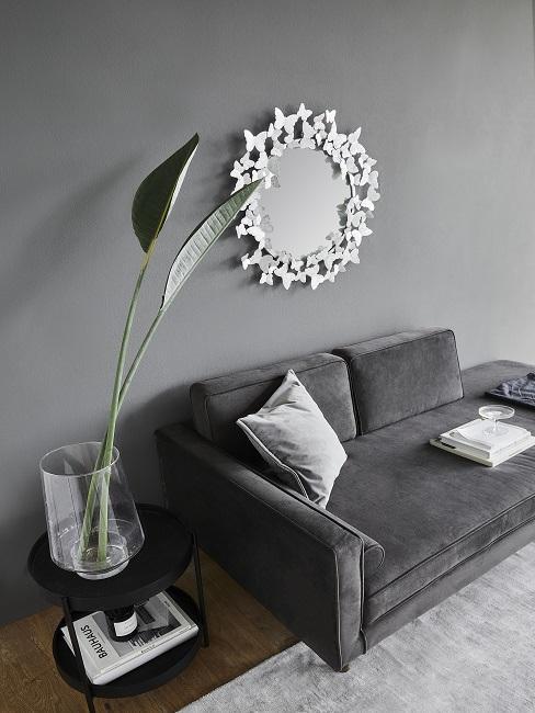 Moderne Einrichtung Wandfarbe grau mit grauem Sofa, Teppich und schwarzem Tisch