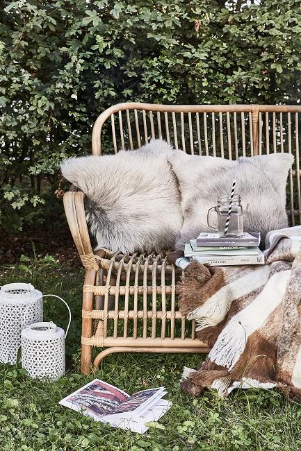 Bambus Bank im Garten mit gemütlichen Textilien und daneben zwei weißen Metalllaternen als Deko