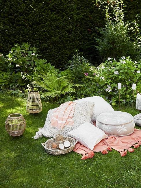Design Garten Wiese und Büsche neben Windlichtern, Decken und Kissen