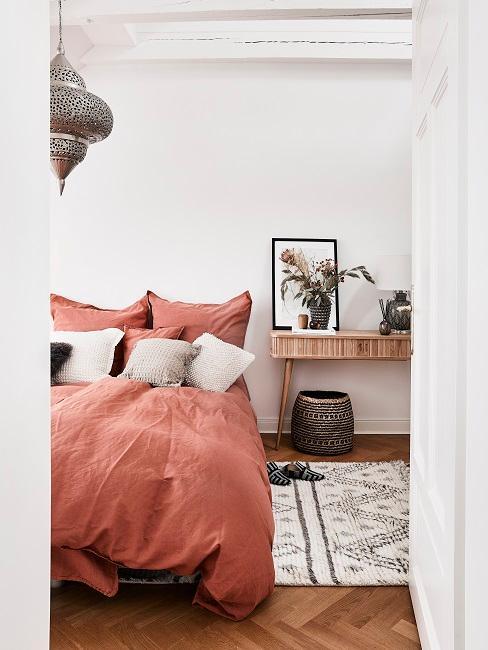 Boho Style Schlafzimmer mit roter Bettwäsche, orientalischer Pendelleuchte und gemustertem Teppich