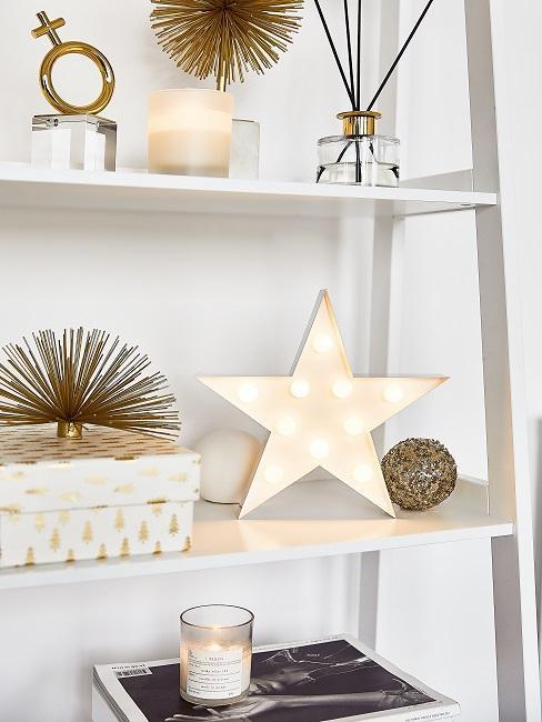 Weißes Regal in Weiß Gold dekoriert mit Zeitschriften Boxen einer Kerze und einem leuchtenden Stern im weihnachtlichen Look