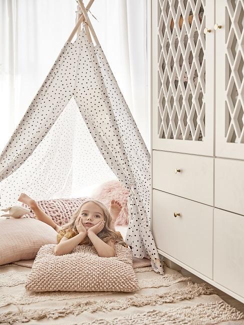 Design Kinderzimmer Mädchen aus Kissen unter Tipi neben weißem Schrank