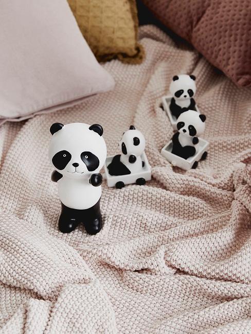 Decke in Rosa mit Kissen und kleinen Panda Figuren als Spielzeug im Luxus Kinderzimmer