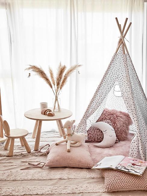 Tipi Zelt mit rosa Kissen und Kuscheltier auf einem passenden Teppich, danebem ein Tisch mit Stuhl aus Holz