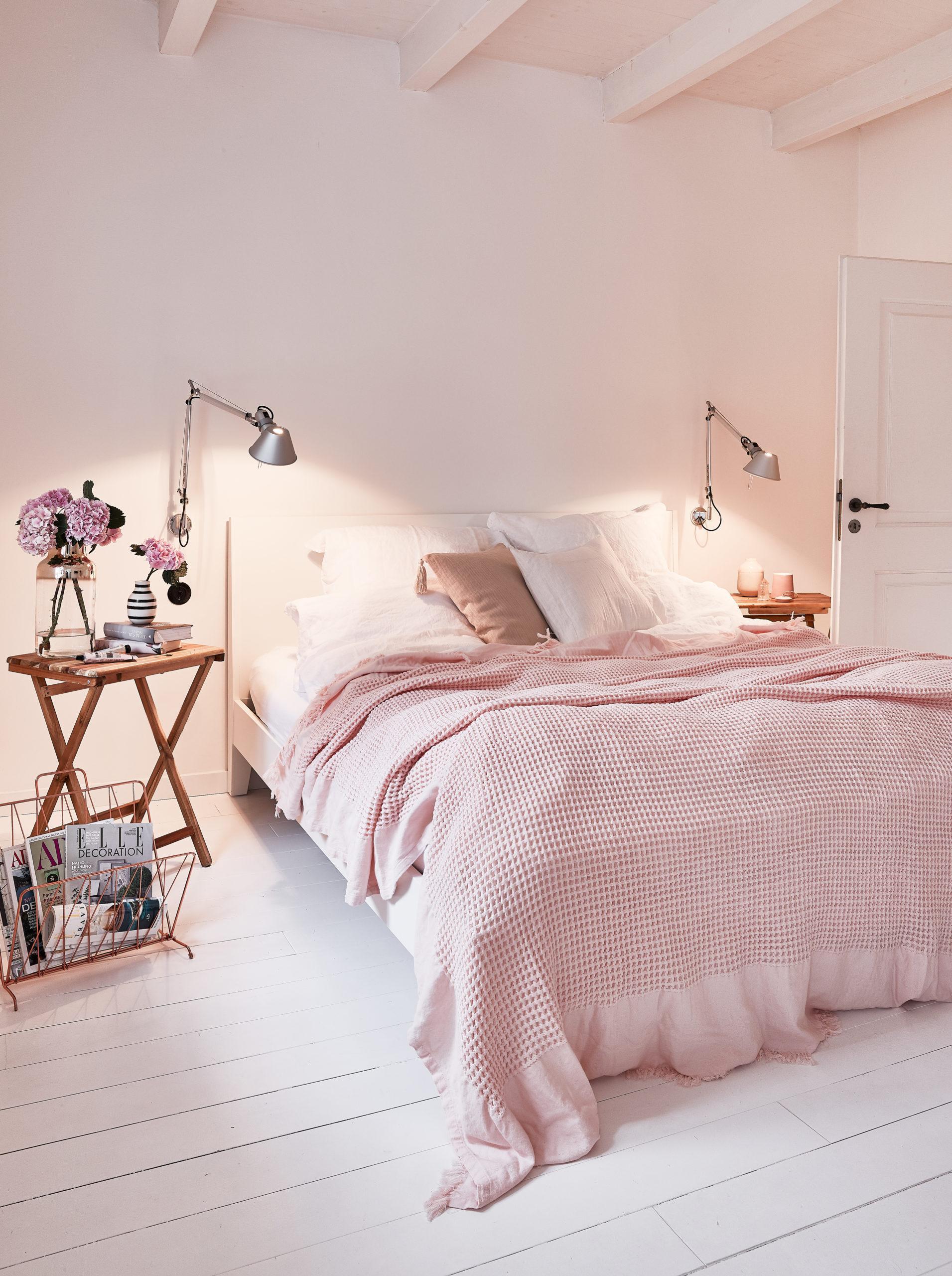 Luxus Schlafzimmer in Rosa mit Wandleuchten, vielen Kissen und gemütlicher Deko