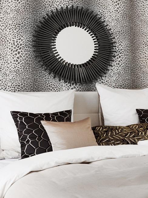 Schlafzimmer mit einer tapezierten Wand hinter dem Bettkopf sowie einem dekorativen Spiegel
