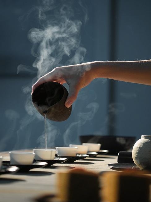 Teezeremonie Tassen in denen Tee aufgefüllt wird