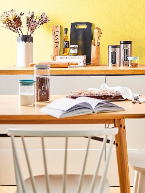 Holztisch vor heller Küchenzeile mit Dekoelementen vor gelber Wand