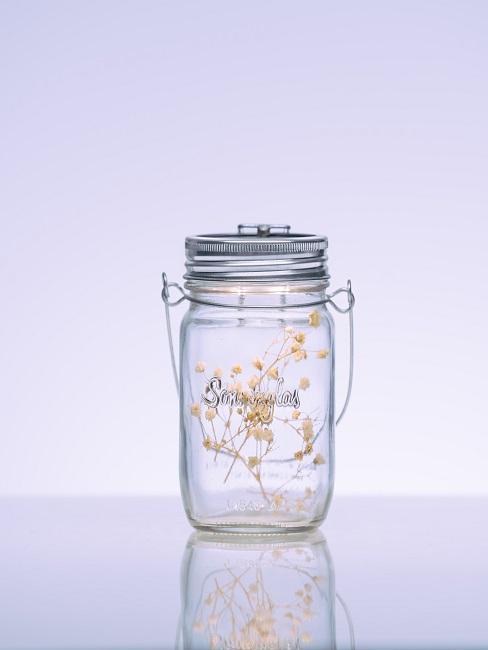 Frühlingsdeko im Glas mit Blumen und einem Sonnenglas.