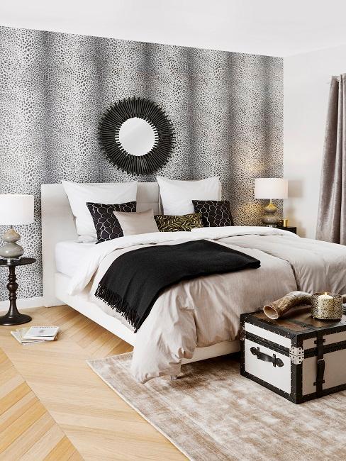 Kolonialstil Schlafzimmer im Afrika Style mit gepunkteter Tapete, braun-weißer Bettwäsche, Truhe und Sonnenspiegel