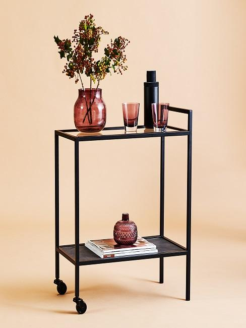 Glass vase on trolley decorated with branches