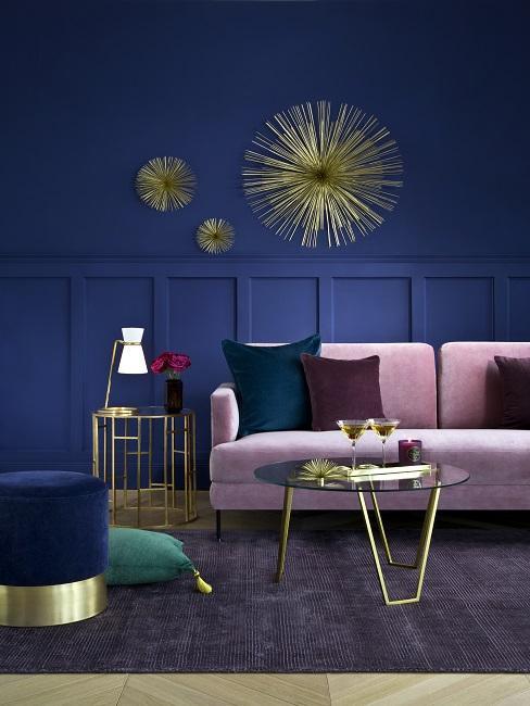 Art Déco Stil Wohnzimmer mit blauer Wand, rosafarbenem Sofa und goldener Wanddeko