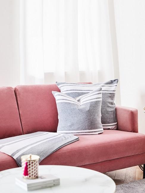 Rosa samt Couch mit grauen Kissen