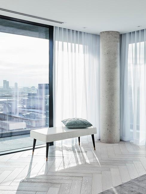 Weiße Sitzbank und grünes Kissen vor großem Fenster