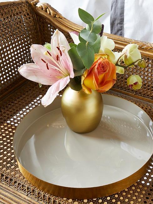 Goldene Vase mit Blumen auf goldenem Tablett