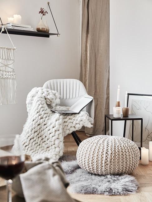Sessel mit Wollplaid neben Pouf