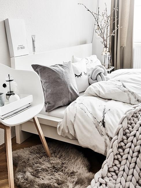 Bett mit weißer Bettwäsche und grauen Kissen